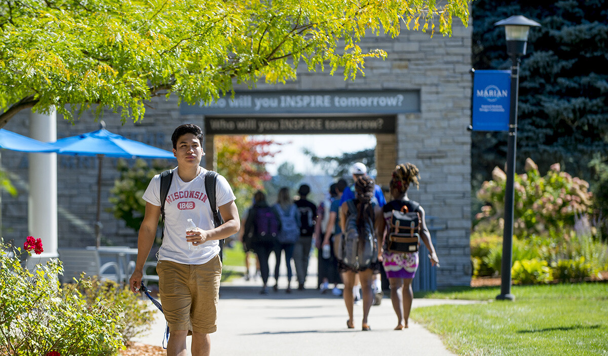 Marian University students walking outside on the campus. Apply for financial aid today.