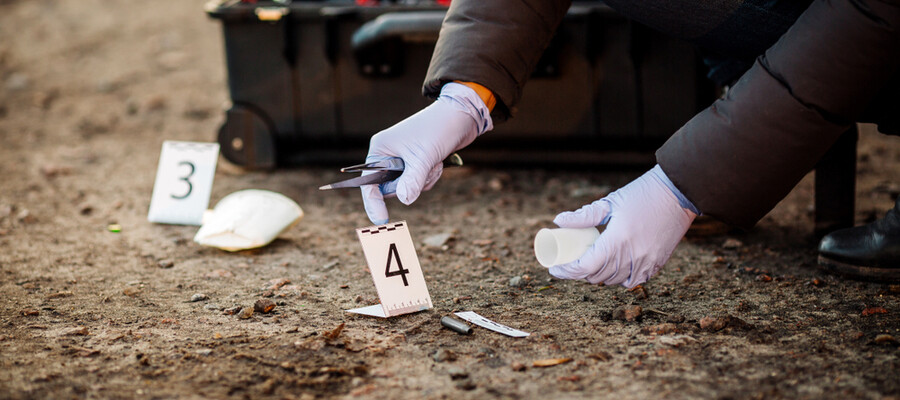 A crime scene analyst collects evidence at a crime scene.