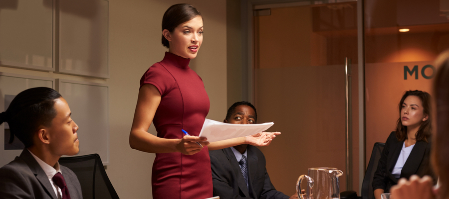 A business unit manager stands in a conference room as her team sits listening to her report on a project.